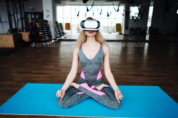 Woman in yoga class with VR helmet - Stock Photo - Images