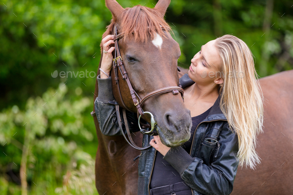 Young woman with her arabian horse standing in the field - Stock Photo - Images