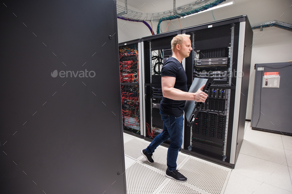 Male Technician Carrying Blade Server While Walking In Datacente - Stock Photo - Images