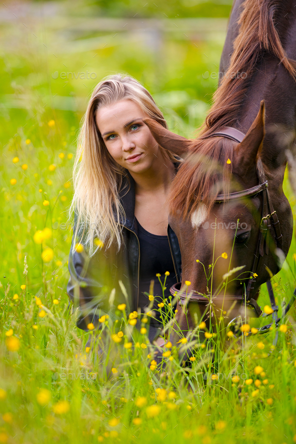 Smiling woman sits in the meadow with her arabian horse - Stock Photo - Images