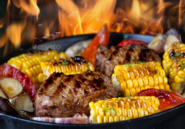 Fried meat and corn with vegetables in a frying pan on fire - Stock Photo - Images