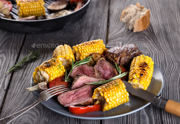 Fried meat and corn with vegetables on a plate - Stock Photo - Images