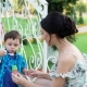 Young Dark-haired Man and Woman Are Teaching Their Little Son To Blow Bubbles in Park in Summer Day - VideoHive Item for Sale