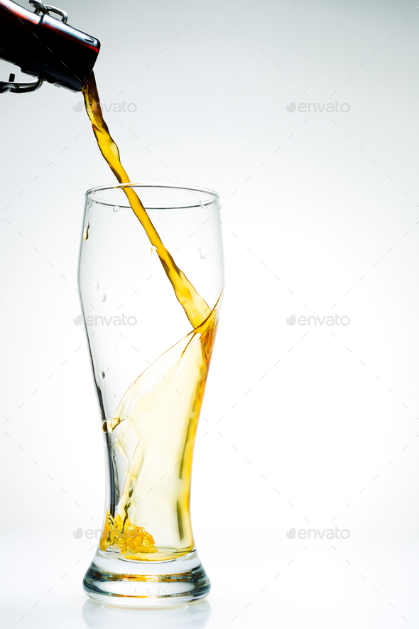 Beer is pouring from a bottle - Stock Photo - Images
