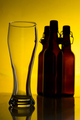 Empty beer glass with beer bottles on color background