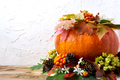 Fall table centerpiece with pumpkin and cones, copy space