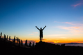 Man celebrating sunset with arms outstretched in mountains