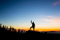 Man celebrating sunset in mountains with arms outstretched