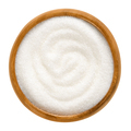 Fine granulated white sugar in wooden bowl over white