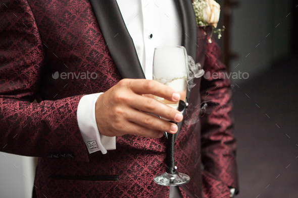 Close up of man holding a glass of champagne in hand - Stock Photo - Images