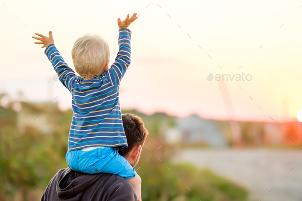Father and son outdoor portrait in sunset sunlight - Stock Photo - Images