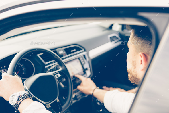 Young man uses automotive navigation system - Stock Photo - Images