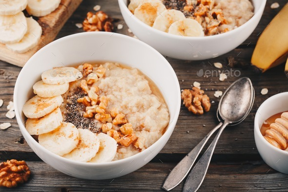 healthy breakfast bowl. oatmeal with banana, walnuts, chia seeds and honey - Stock Photo - Images