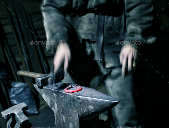 Hands of blacksmith with hammer blowing warmed horseshoe - Stock Photo - Images