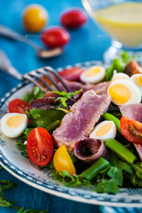Tuna salad with tomatoes, boiled eggs, onion, anchovy and lettuc - Stock Photo - Images