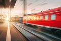 Modern high speed red passenger train moving through railway sta - PhotoDune Item for Sale