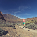 Young woman trail running in mountains on sunny day