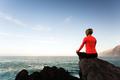 Woman meditating in yoga pose, ocean view