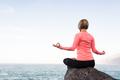 Yoga girl meditating and relaxing in yoga pose, ocean view