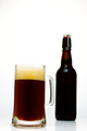 Dark beer in a glass and a bottle of beer on a white background