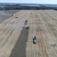 Aerial Distant Shooting of the Work of Three Combines and a Tractor on the Wheat Field - VideoHive Item for Sale