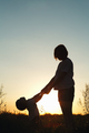 Silhouette of a woman with her child at sunset.