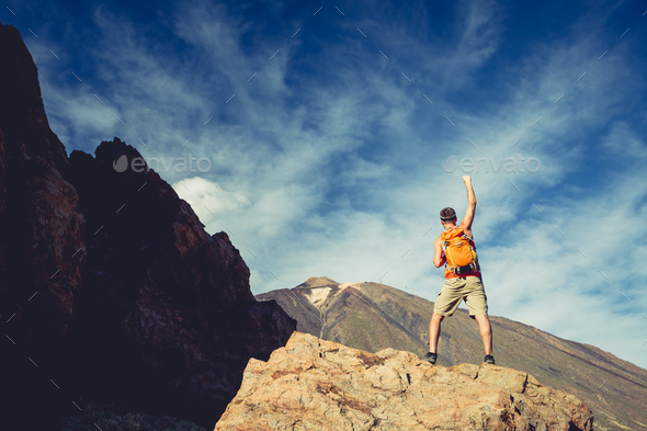 Man celebrating success in mountains, arms outstretched - Stock Photo - Images