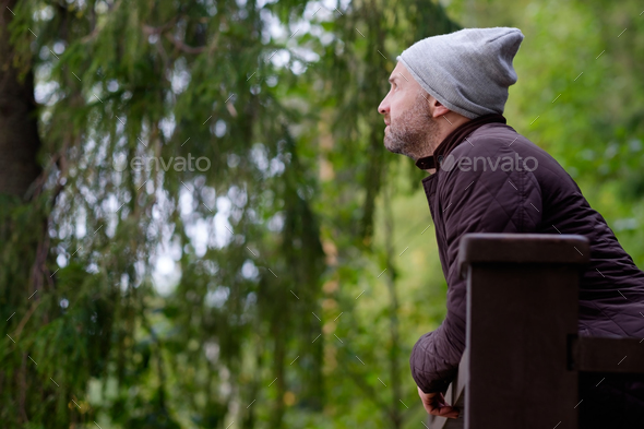 handsome mature man smiling in warm hat and jacket looking aside - Stock Photo - Images
