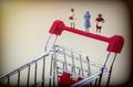 Miniature figures of women on a shopping cart