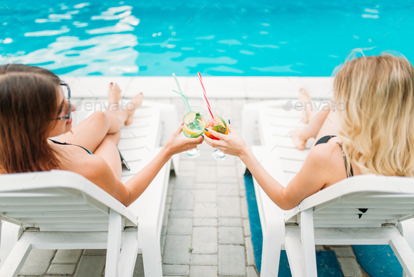 Two sexy girls relax with cocktails on deck chairs - Stock Photo - Images