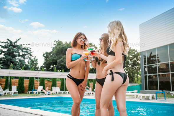 Sexy tanned girls near the swimmimg pool - Stock Photo - Images