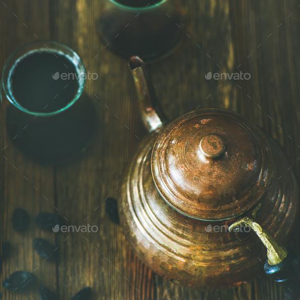 Oriental teapot, black tea in glasses and raisins, square crop - Stock Photo - Images
