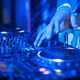 DJ playing music at mixer on colorful blurred background - PhotoDune Item for Sale