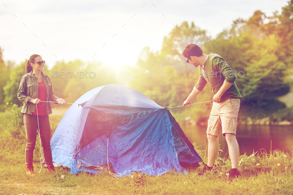 happy couple setting up tent outdoors - Stock Photo - Images