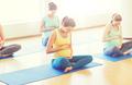 happy pregnant women exercising yoga in gym
