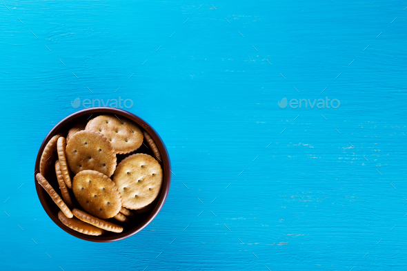 Bowl with crispy crackers on blue background - Stock Photo - Images