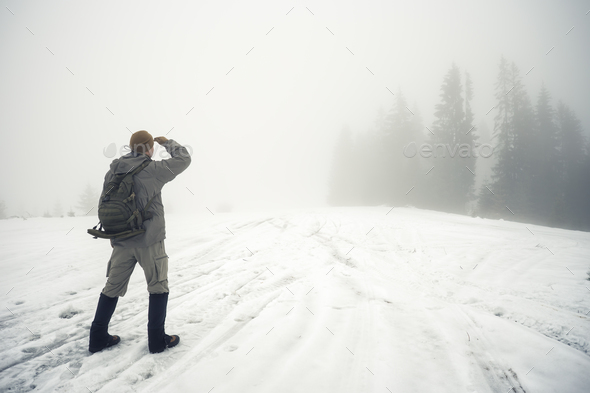 Man with backpack in the winter mountains peers into the foggy d - Stock Photo - Images