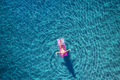 Aerial view of young woman swimming on the pink inflatable mattr - PhotoDune Item for Sale