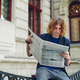 Young reddish man reading newspaper near old style building - PhotoDune Item for Sale