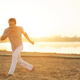 Athletic capoeira performer making movements on the beach - PhotoDune Item for Sale