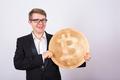 Happy businessman holding big golden bitcoin on white background.