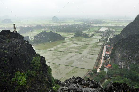 Rice fields, limestone rocks and mountaintop pagoda from Hang Mua Temple, Ninh Binh, Vietnam - Stock Photo - Images