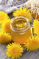 Dandelion jam in a jar and fresh flowers