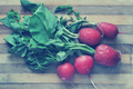 Red radishes on a cutting board. Toned