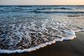 Waves approaching beach sand during golden sunset