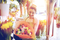 smiling florist woman with bunch at flower shop