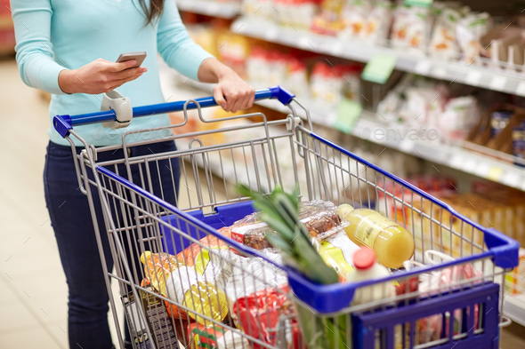 woman with smartphone buying food at supermarket - Stock Photo - Images