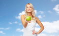 happy young woman with green apple over blue sky
