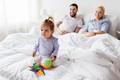 happy child with toys and parents in bed at home