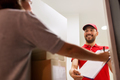 deliveryman and customer with parcel boxes at home